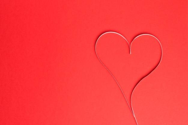 Cœur de papier sur fond rouge