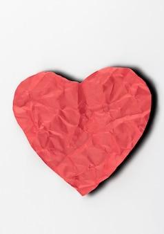 Coeur de papier froissé sur fond blanc.