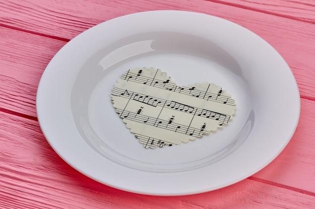 Coeur de papier avec des notes de musique sur assiette.