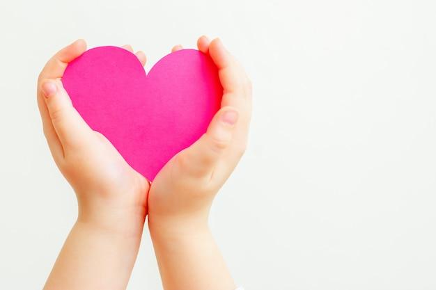 Coeur de papier rose dans les mains de l'enfant