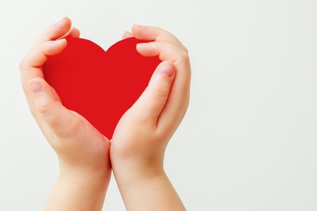 Coeur de papier rouge dans les mains de l'enfant