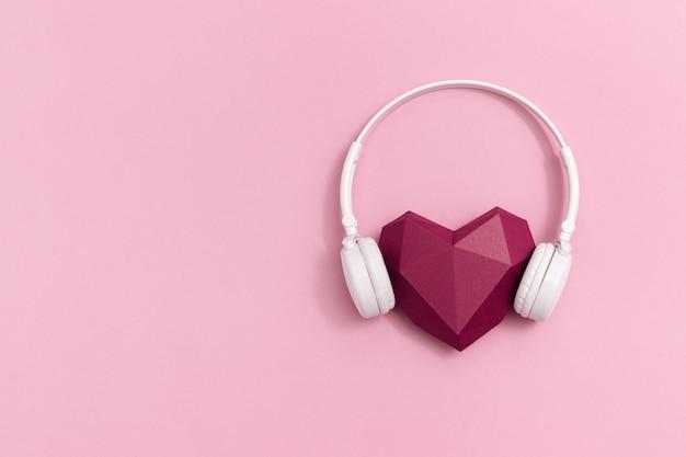 Coeur de papier rouge foncé 3d dans des écouteurs blancs