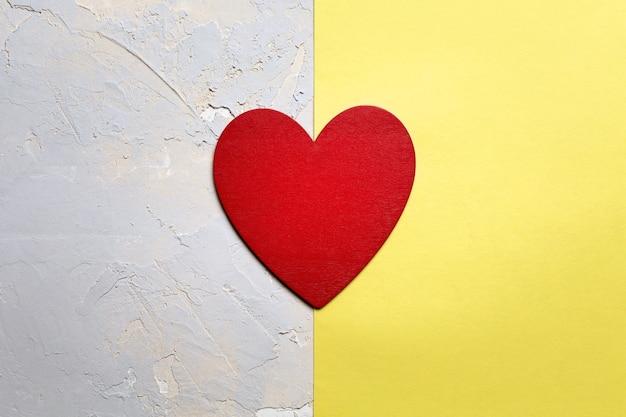 Coeur peint en rouge sur papier jaune, carte minimaliste de saint valentin en couleur de l'année
