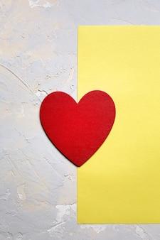 Coeur peint en rouge sur papier jaune sur fond texturé gris, carte minimaliste de saint valentin en couleur pantone 2021 de l'année