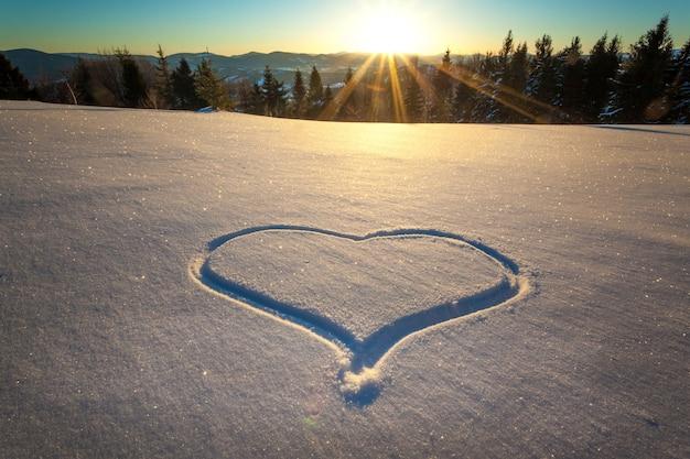 Coeur piétiné sur la neige avec les pieds dans une congère sur une colline avec une vue magnifique sur la forêt de conifères et les chaînes de montagnes par une journée ensoleillée et glaciale pendant des vacances de ski. place pour le texte