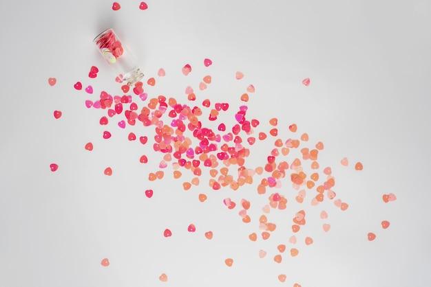 Cœur en polyuréthane blanc sur le fond d'une dispersion de paillettes. carte postale. la saint valentin.