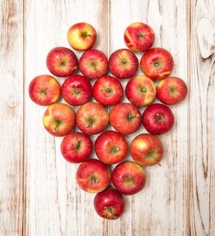 Coeur de pommes sur fond de bois rustique. notion d'amour. couleurs vives