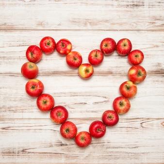 Coeur de pommes rouges sur fond de bois rustique. notion d'amour. couleurs vives