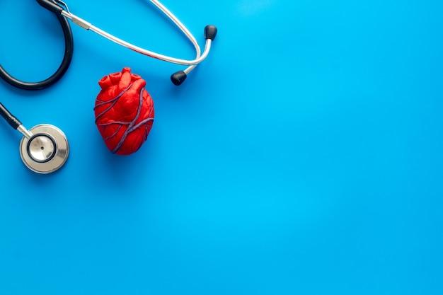 Coeur près du tonomètre de pilules, traitement sur bleu