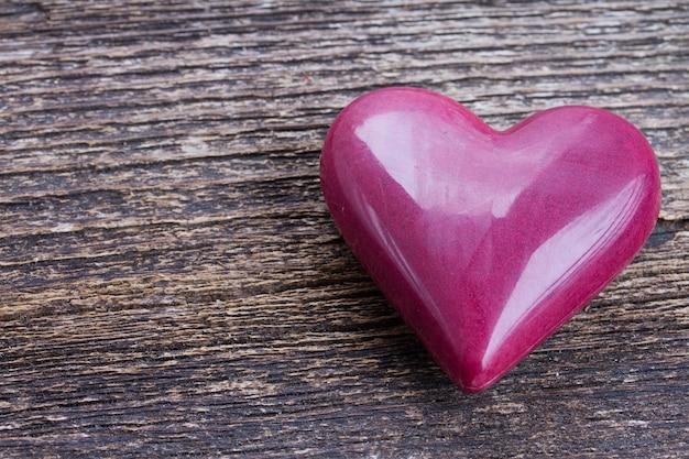 Un coeur rose marsala portant sur fond de bois