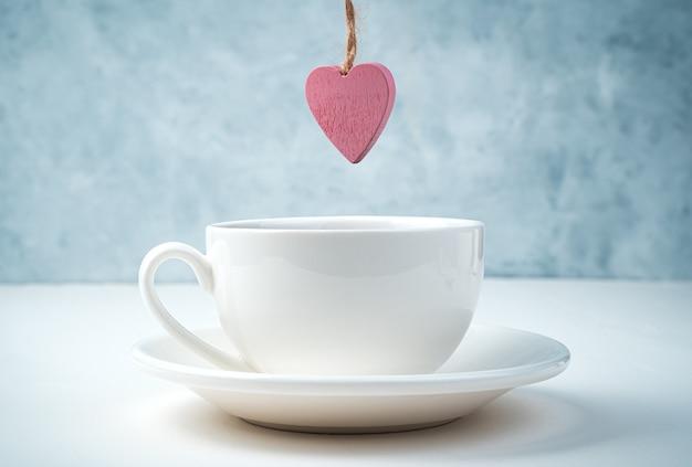 Un cœur rose pèse sur une tasse à café et une soucoupe