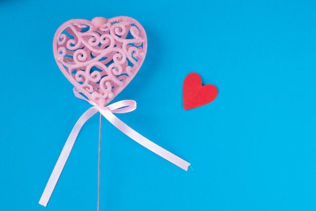Coeur rose avec petits coeurs rouges sur fond bleu