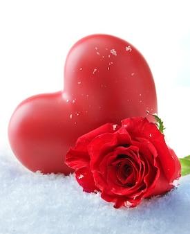 Coeur et rose rouge sur la neige