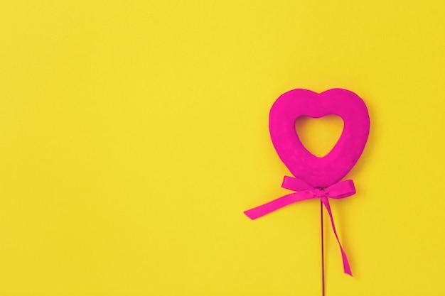 Coeur rose sur une surface jaune, arc, amour