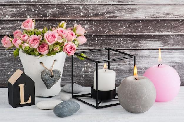 Coeur, roses roses en pot de béton avec bougies
