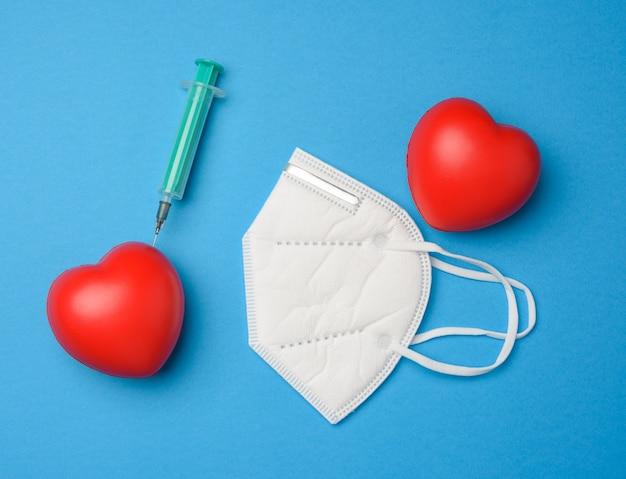 Coeur rouge et une aiguille coincée d'une seringue en plastique dedans, masque blanc sur fond bleu