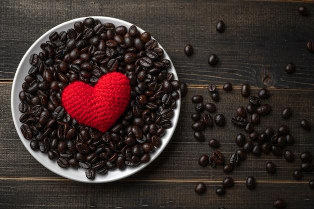 Coeur rouge sur beaucoup de grains de café torréfiés sur plaque sur une table en bois. expresso noir fort, grains de café