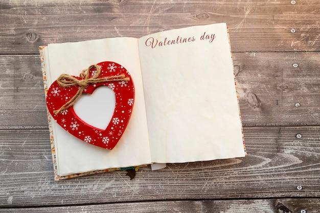 Coeur rouge en bois avec place pour photo sur la page centrale du bloc-notes vintage
