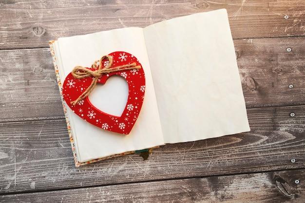 Coeur rouge en bois avec place pour photo sur la page centrale du livre