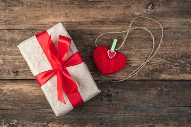 Coeur rouge et boîte-cadeau sur fond en bois.