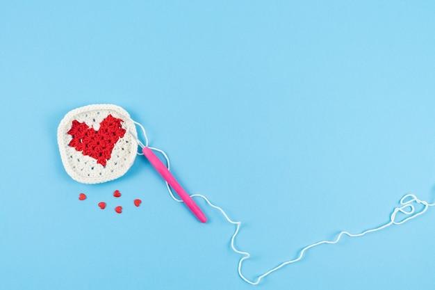 Coeur rouge avec bordure blanche au crochet sur fond bleu.