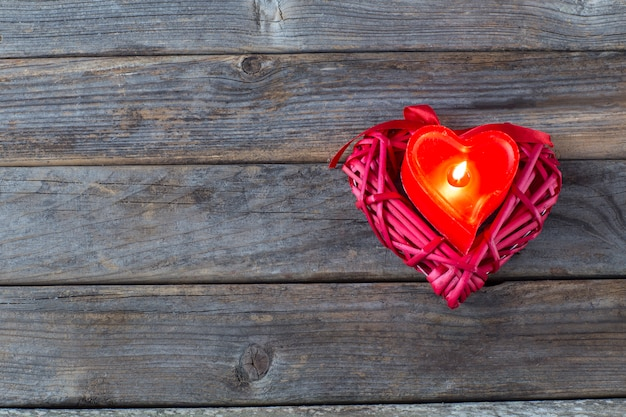 Un coeur rouge et une bougie en forme de coeur rouge