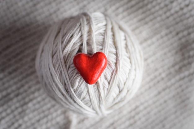 Coeur rouge et une boule de fils sur un fond tricoté