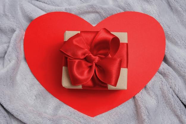 Coeur rouge avec un cadeau sur un couvre-lit gris ou une couverture, vue du dessus