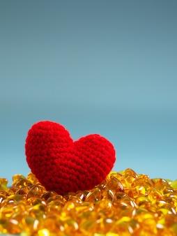 Coeur rouge sur capsules d'huile de poisson sur fond bleu. oméga-3 et stéthoscope sains.