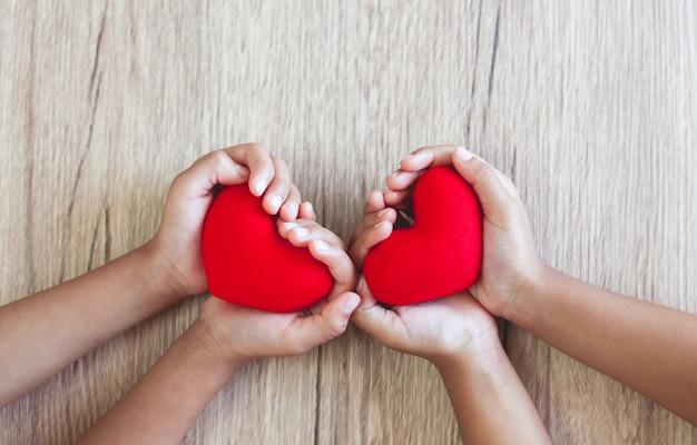 Coeur rouge chez l'enfant des mains sur le fond de la table en bois avec amour et harmonie