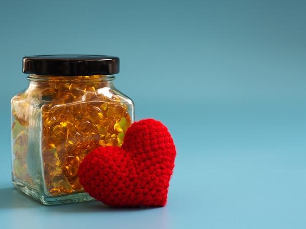 Coeur rouge à côté de capsules d'huile de poisson dans des bouteilles en verre sur fond bleu.