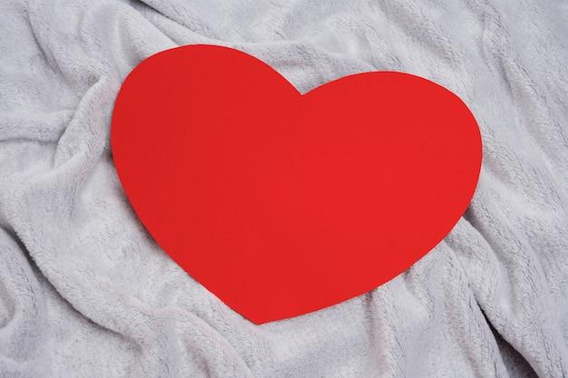 Coeur rouge sur un couvre-lit gris ou une couverture, vue du dessus