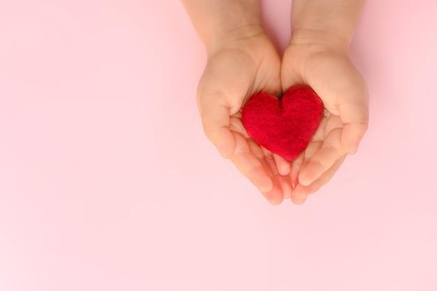 Coeur rouge dans l'amour et la famille des mains de l'enfant