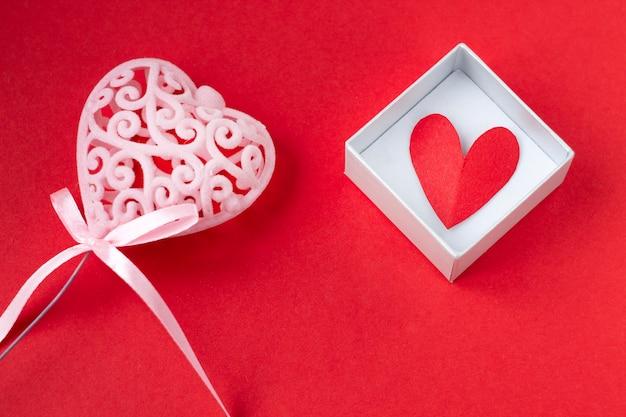 Coeur rouge dans une boîte cadeau sur fond rouge