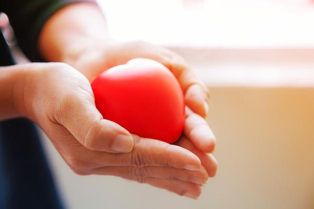 Coeur rouge dans les deux mains de la femme dans le fond du costume noir, représente les mains aidantes