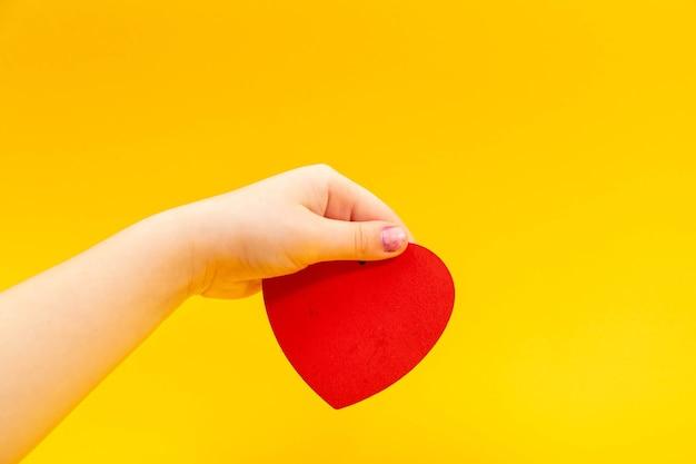 Coeur rouge dans la main de l'adolescent sur jaune. concept de la saint-valentin.