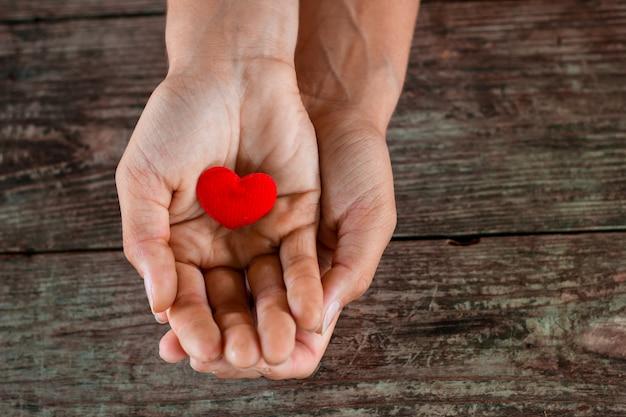 Coeur rouge dans une main féminine sur fond en bois.