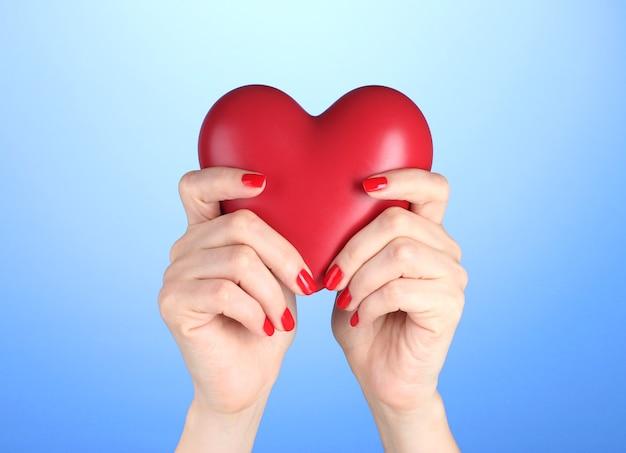 Coeur rouge dans les mains de la femme sur fond bleu