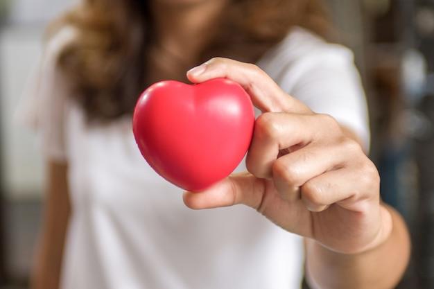 Coeur rouge dans les mains de la femme