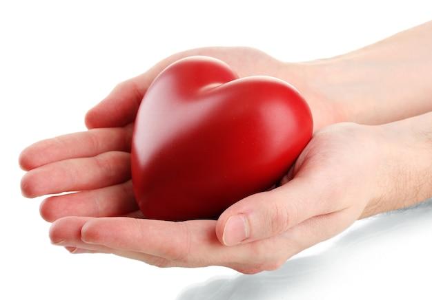 Coeur rouge dans les mains de l'homme, isolé sur une surface blanche