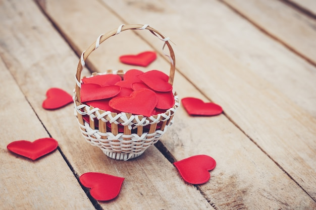 Coeur rouge dans le panier sur la table en bois pour la saint valentin et le concept de l'amour avec l'espace de la copie.