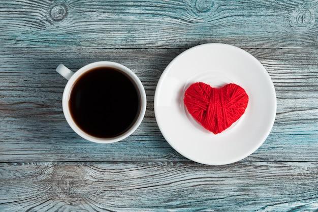 Un cœur rouge dans une soucoupe blanche à côté d'une tasse de café.
