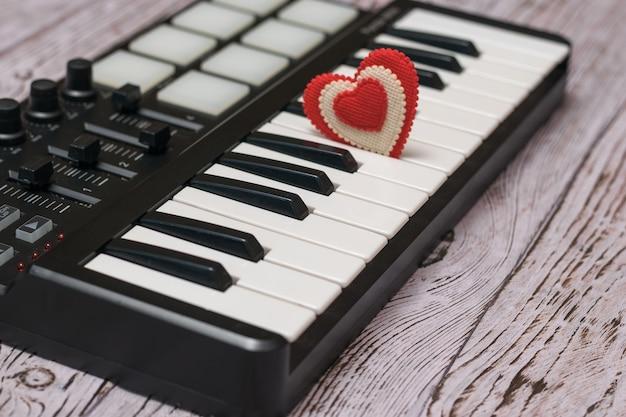 Un cœur rouge dans les touches d'un mélangeur de musique sur une table en bois