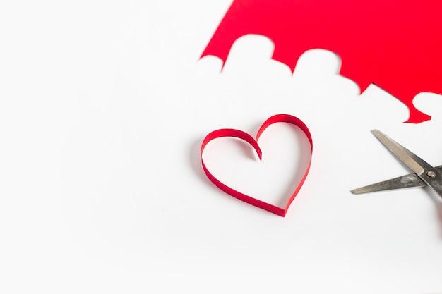Coeur rouge découpé dans du papier, des ciseaux et du carton de couleur sur un fond blanc clair. composition saint-valentin. bannière. mise à plat, vue de dessus.