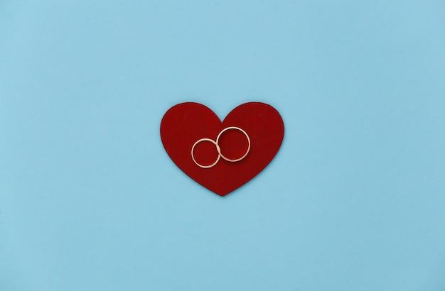 Coeur rouge avec deux anneaux d'or sur fond bleu.