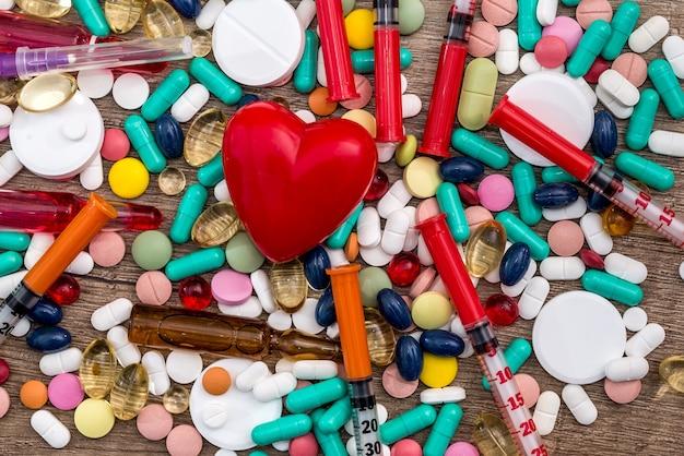 Coeur rouge sur différentes pilules avec des seringues