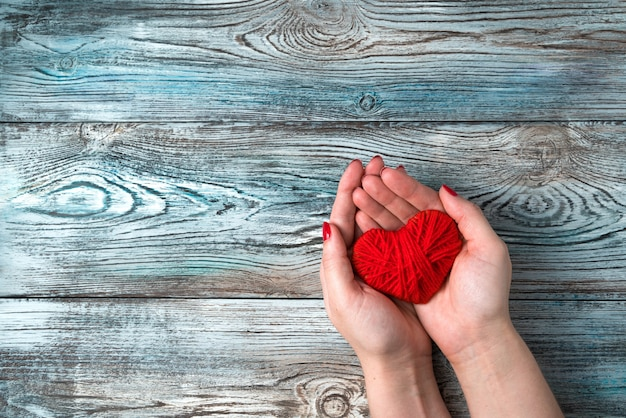 Coeur rouge entre les mains d'une femme sur un fond en bois gris-bleu.