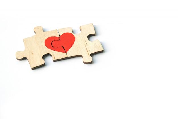 Un cœur rouge est dessiné sur les pièces du puzzle en bois se trouvant côte à côte, isolées sur fond blanc. amour . saint valentin. espace de copie.