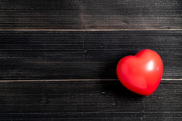 Le coeur rouge est placé sur le côté gauche de la table en bois noir. espace de copie pour le texte et le contenu