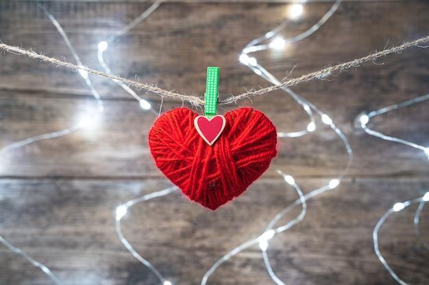 Un coeur rouge est suspendu à une corde sur une guirlande lumineuse.